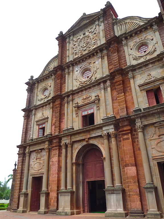 A view of the impressive Bom Jesus Basilica with its red laterite finish, arches and circular windows.