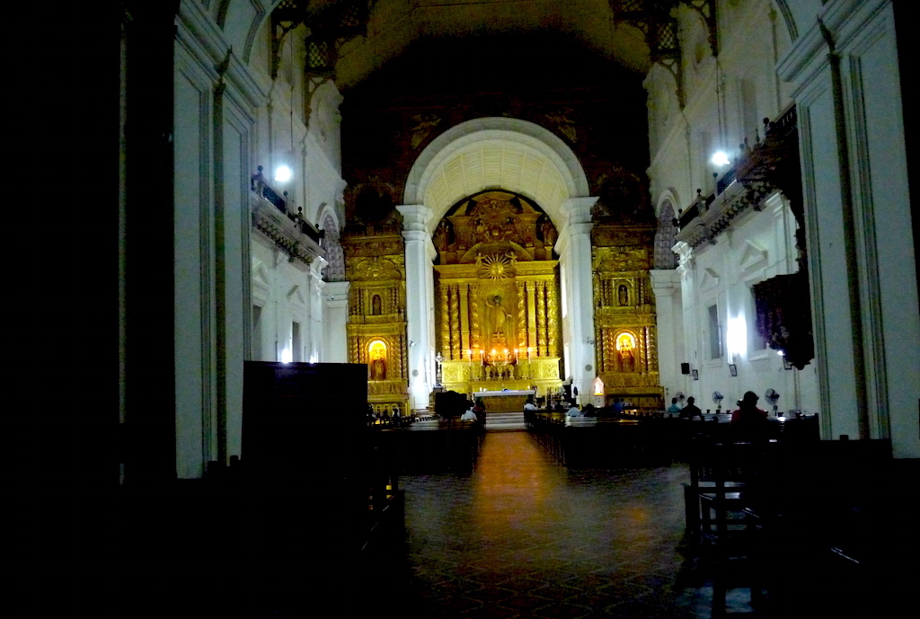 The interiors of Bom Jesus Basilica at dusk. A service is in session. The altar has a statue of St Ignatius of Loyola, an image of Bom Jesus and a sculpture of the Holy Trinity.